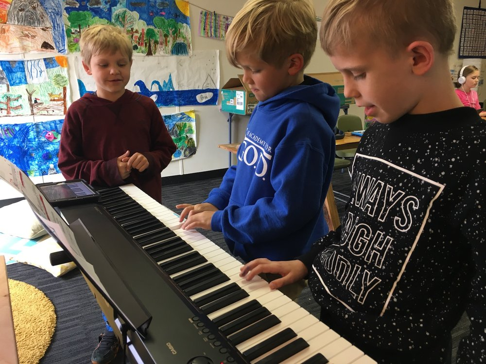 "Students took turn playing ""God is So Good"" on the piano after practicing it on garage band first."