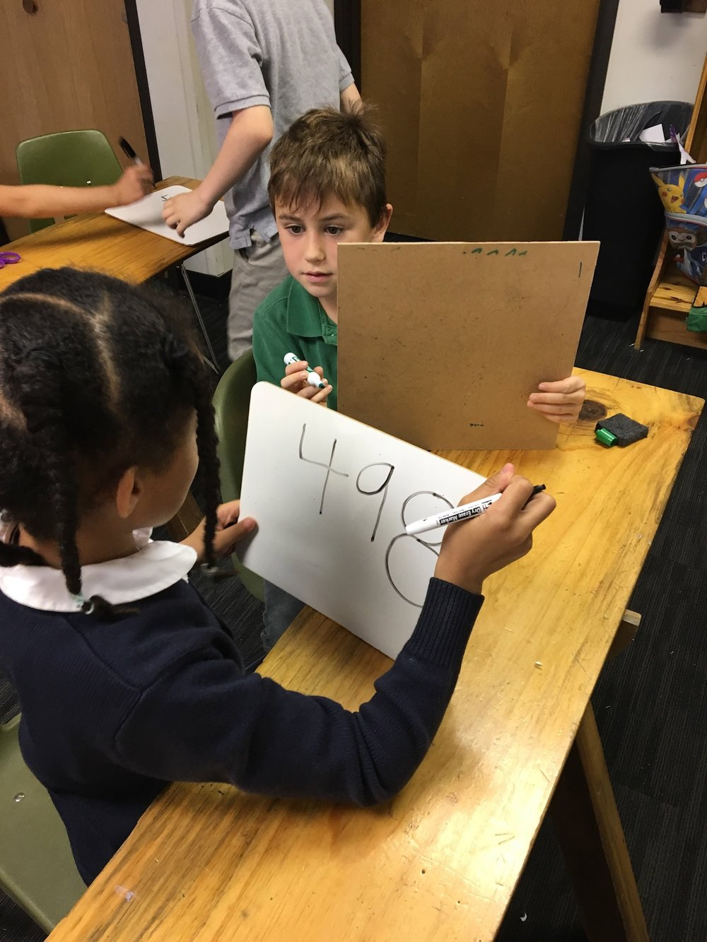 For the first class of 'Make it to the Top' students reviewed place value by playing a game where they had to guess the number their partner came up with. The student that made up the number would tell their partner if they got any digits correct or if a place of a number was correct.