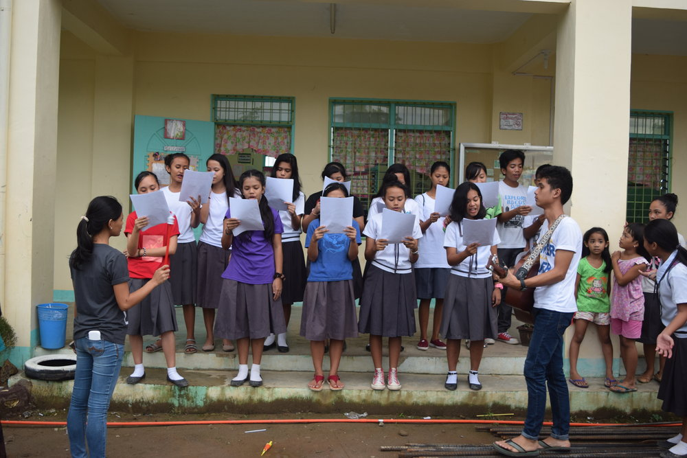 Social Work Intern, Sherelyn Campo (left), and MC lead the Pawing High School weekly girls choir rehearsal.