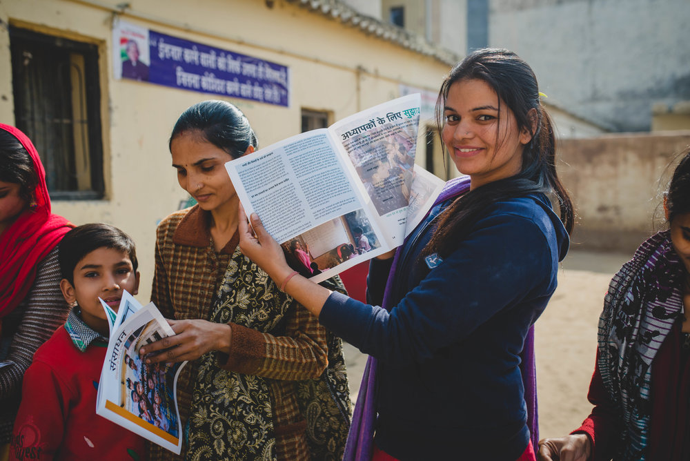 """Sandhya shows off her photo in the """"Resources"""" magazines. The teachers were delighted to see pictures of themselves in a magazine that was created to help them in the classroom."""