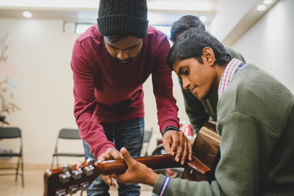 Manohar Paul teaches his students guitar chords during their music class. Manohar has a deep love for both youth and music, which makes this class something the boys look forward to every week.
