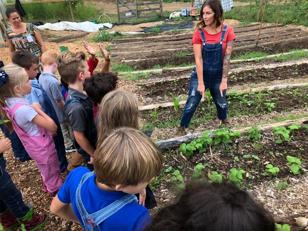 Kim shares her gardening knowledge with students from the Academy for G.O.D. Her passion for growing healthy food is evident and contagious!