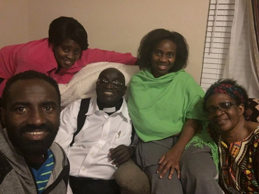 Nyago (bottom left) attends a fellowship of Kenyan believers immigrated to Nashville. They gather in various members' homes and share a potluck meal together before studying the Bible. The man in the center is a retired reverend who lives here with his wife (far right) and children.