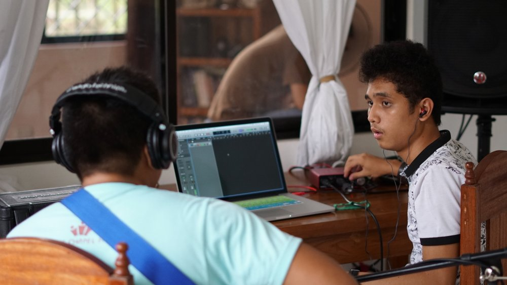 Through his internship program, MC is learning different elements to recording music. Here he mixes another artist as they record the guitar part for a song.