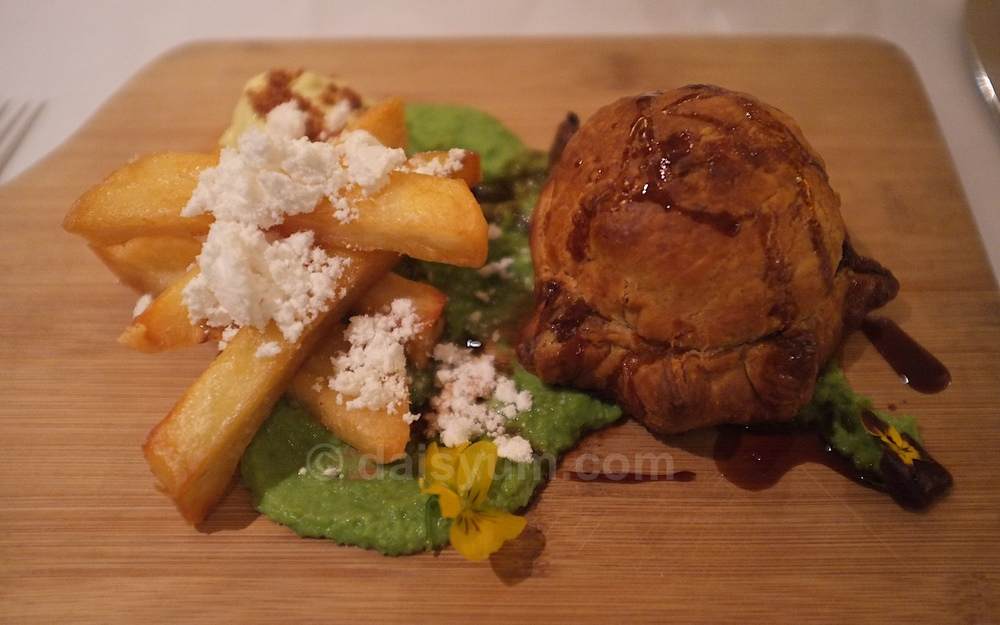 Braised beef pie, pea puree, triple cooked chips, truffle aioli and bacon powder