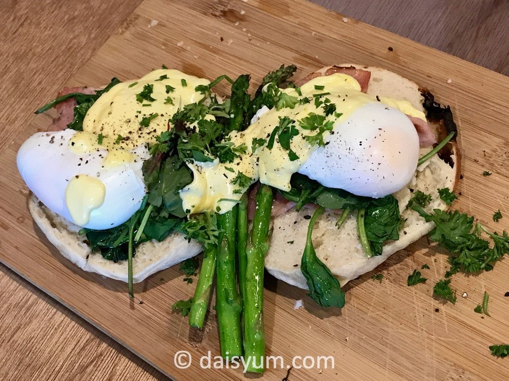 Eggs florentine - poached eggs, asparagus and spinach on bagel with hollandaise sauce