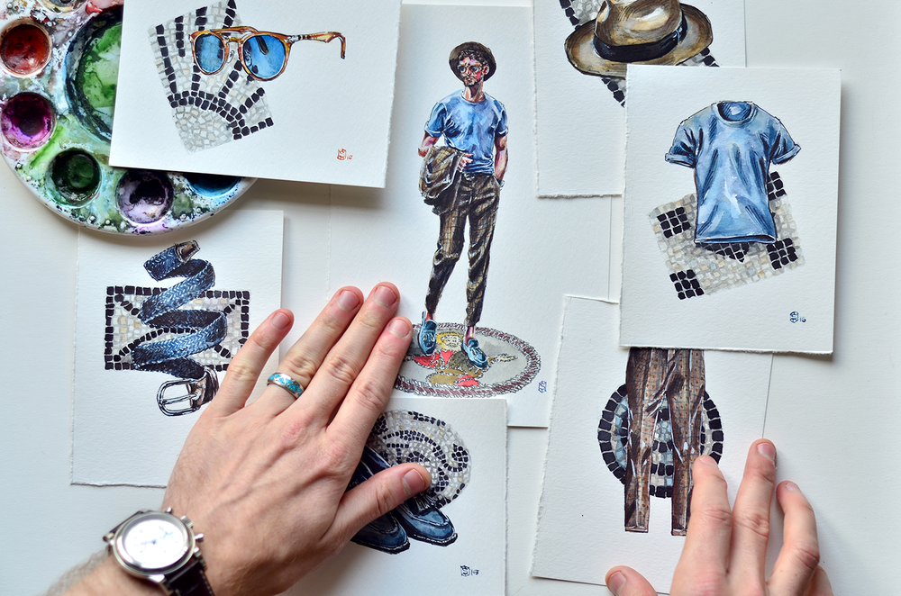 Menswear illustration paintings of the Italian Style laid out on a table with hands in the photo