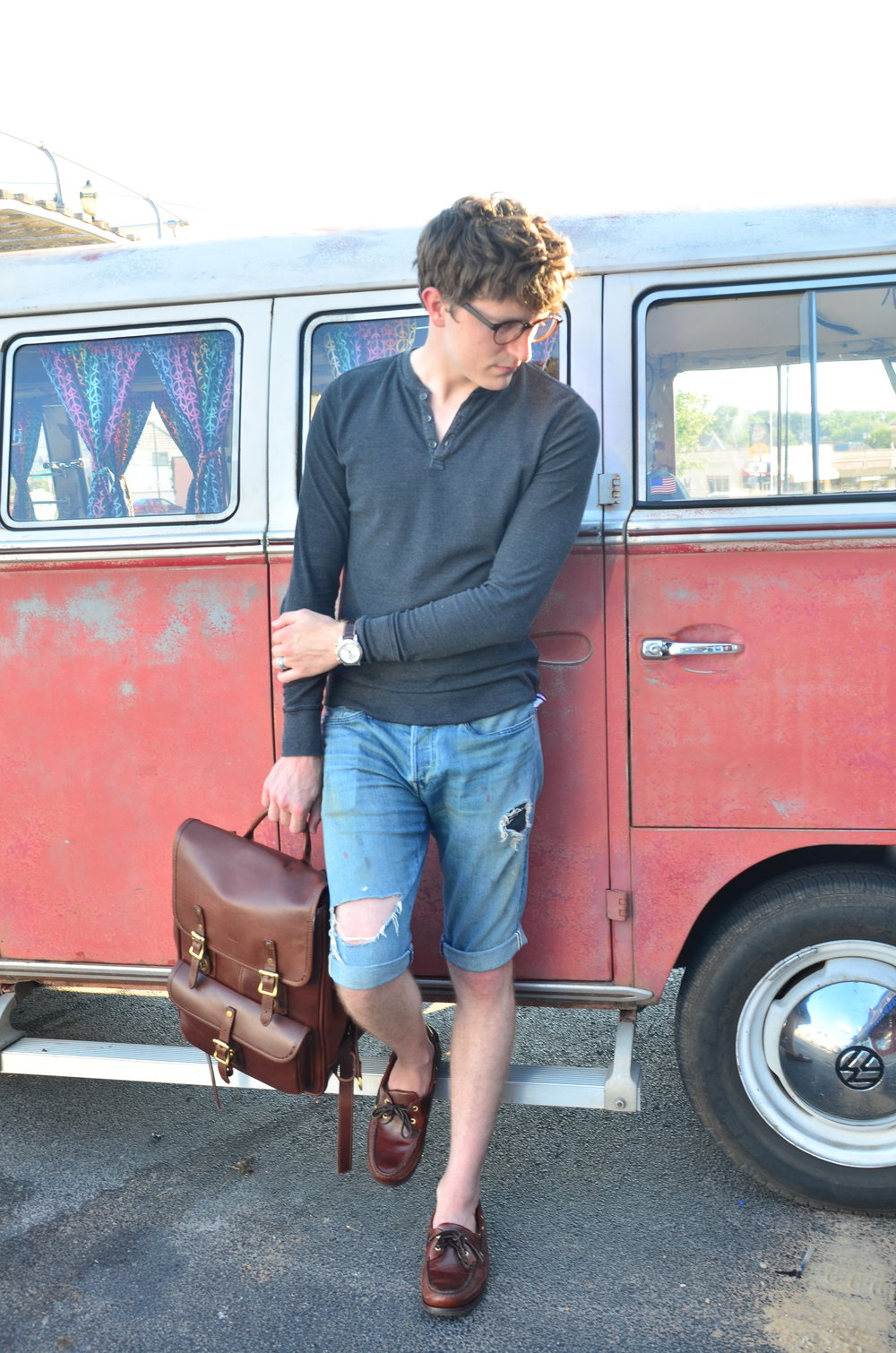 Standing against a VW bus while holding the JW Hulme leather bag