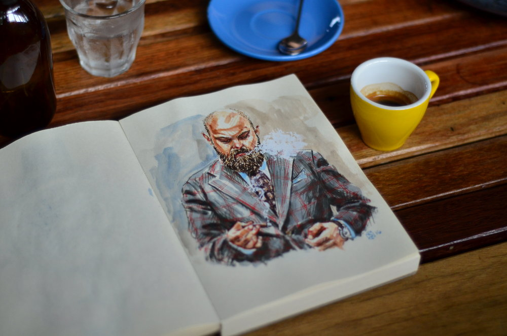 Open sketchbook on a cafe table with espresso