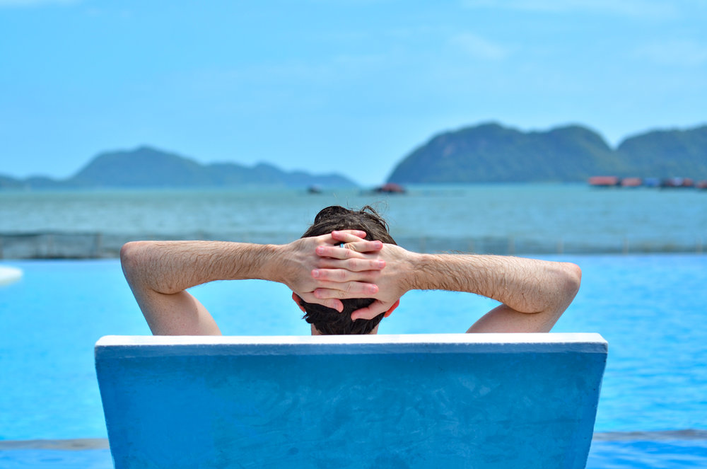 Hands behind head viewing the back of a chair with man reclining on pool chair overlooking the Andaman sea
