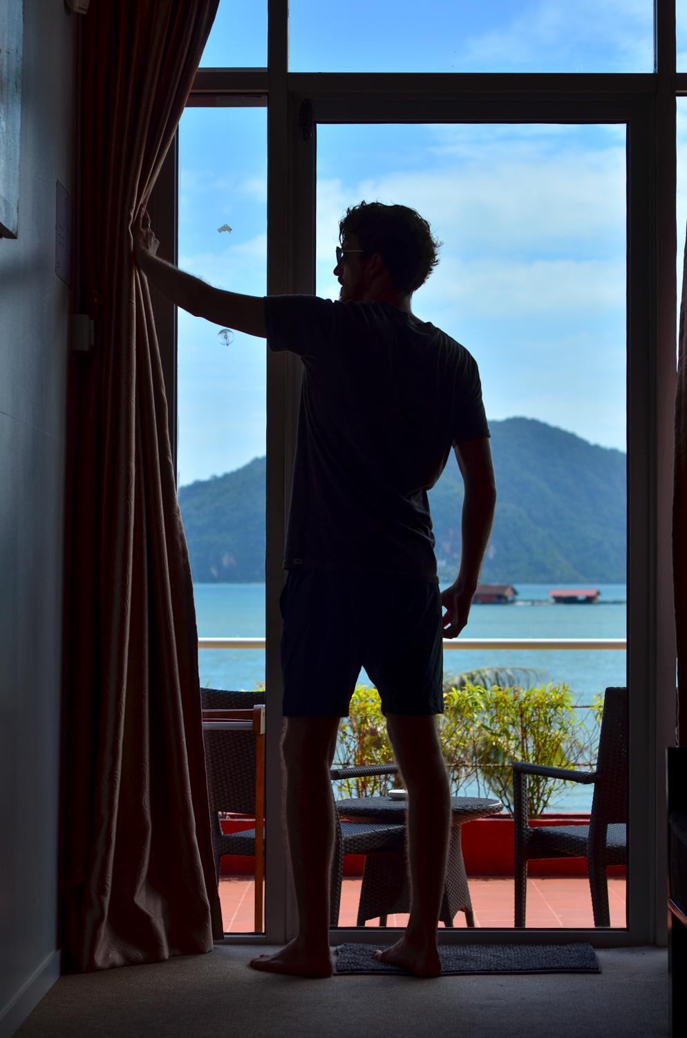 Views from the container stay at Ocean Residence Langkawi. Man pulling back curtains to reveal the Andaman Sea