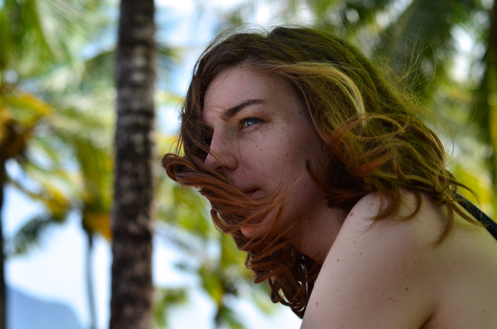 Woman sitting under palm trees with winding blowing her beautiful hair across her face.