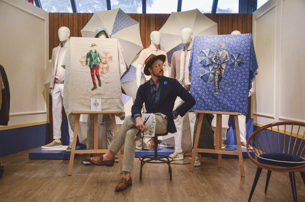Sunflowerman sitting at the Luciano Barbera booth during Pitti Uomo with two live paintings