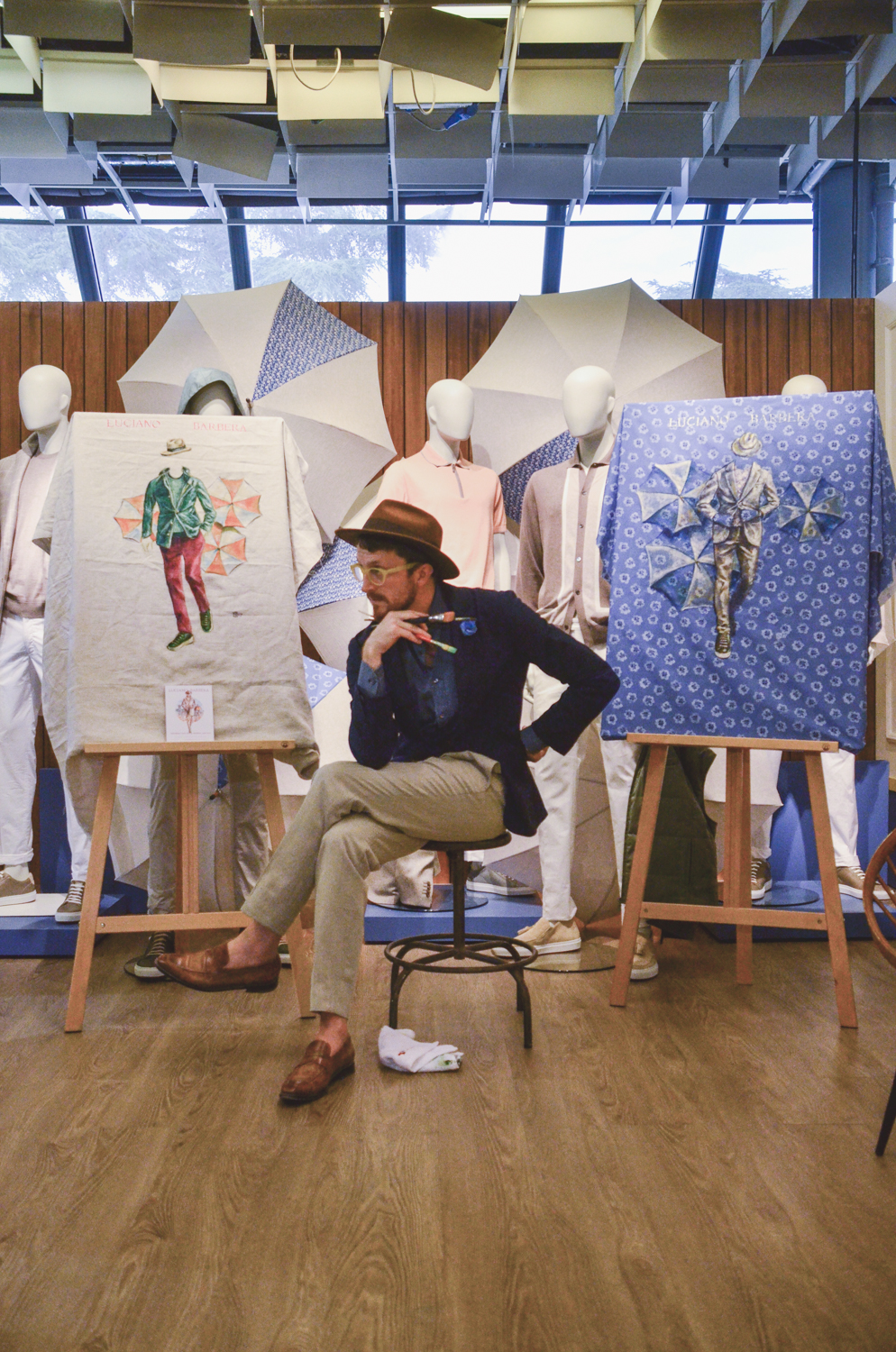 Sunflowerman sitting with his Luciano Barbera paintings on easels