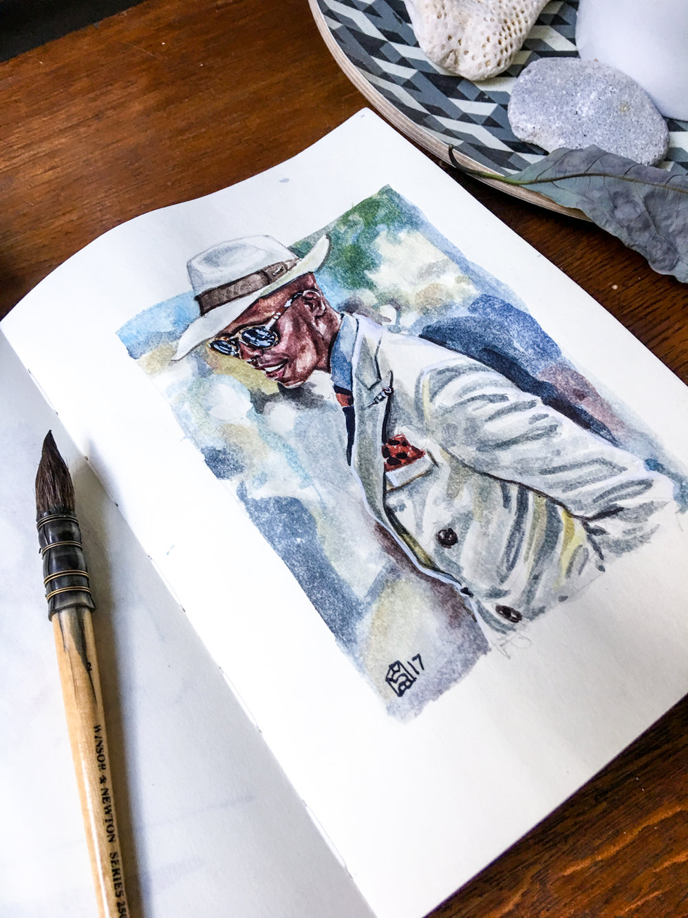 Open sketchbook with men's fashion illustration of Palmer Mutandwa of Button Brothers