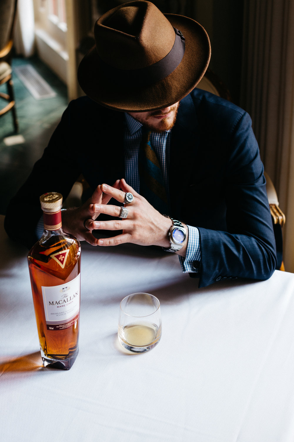 Sunflowerman sitting with a dram and bottle of Macallan Whisky inside The French Room. photo by Collin Sansom