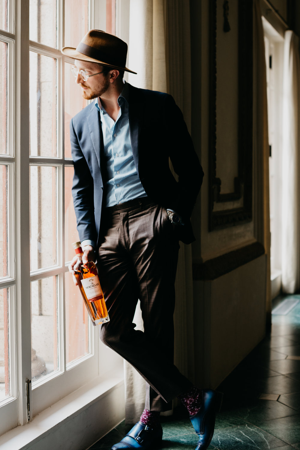 Sunflowerman standing by window with Macallan bottle in hand in The French Room. photo by Collin Sansom