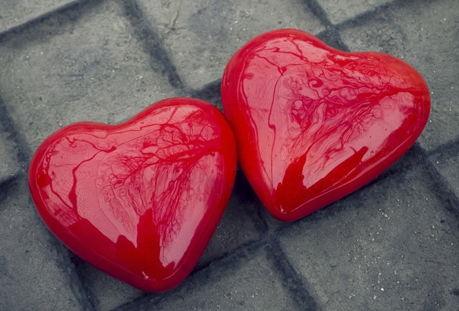 Two shiny red hearts lying beside each other on a tile floor
