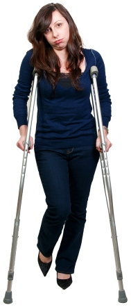 a color photo of a young, frowning brunette woman walking on crutches