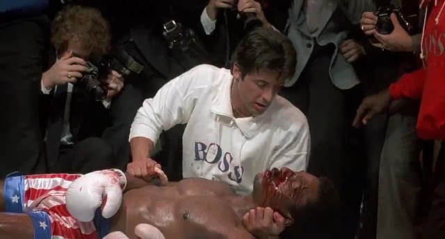 The body of Apollo Creed is held by his friend Rocky.