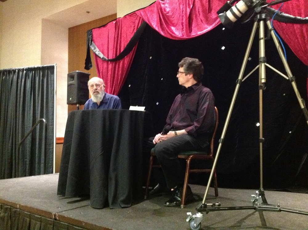 Larry Haas interviewing Eugene Burger's head as it sits on the table.at the lecture