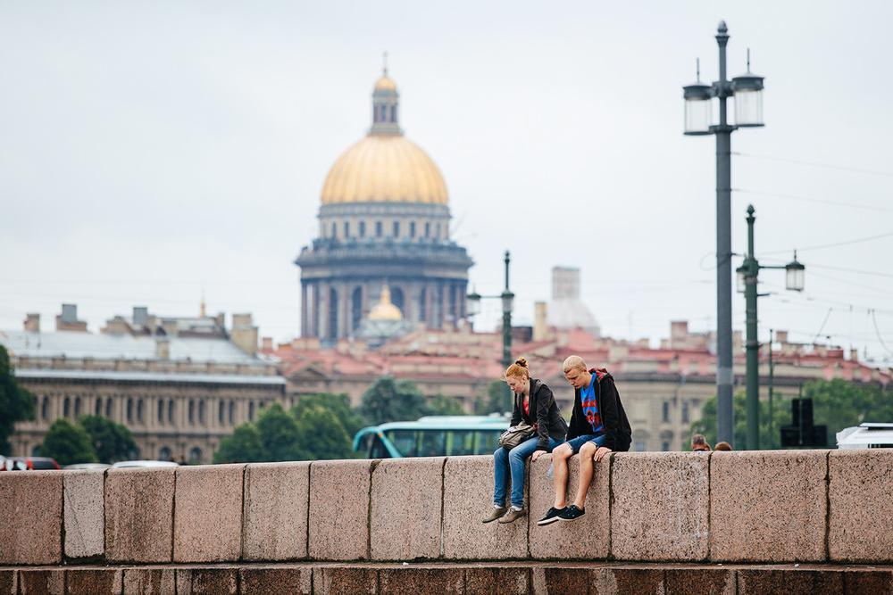 Kids are sitting on the waterfront of Vasilyevsky Island