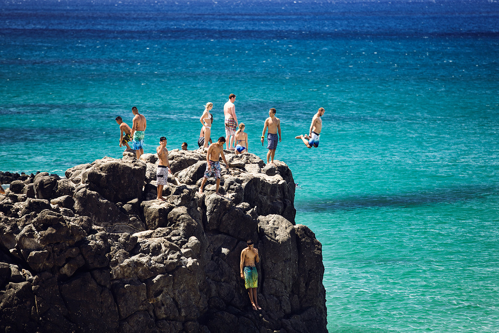 People jump from the rock in Waimea Beach, North Shore Oahu
