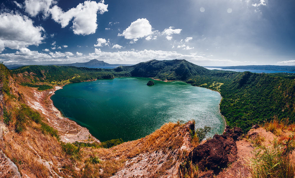 Taal volcano with a lake inside the crater. Water that you see outside/behind volcano is a Tall lake that is in a larger crater surrounding Taal Island.