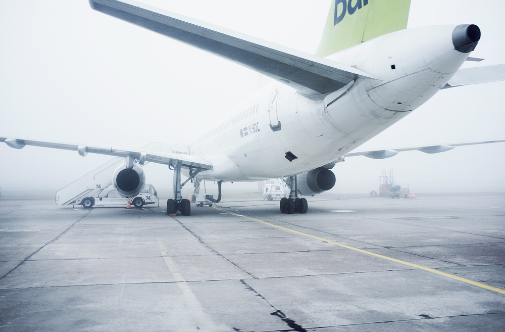 AirBaltic Boeing 757 in foggy airport in Riga, Latvia. The photo was taken form an airport bus approaching the aircraft.