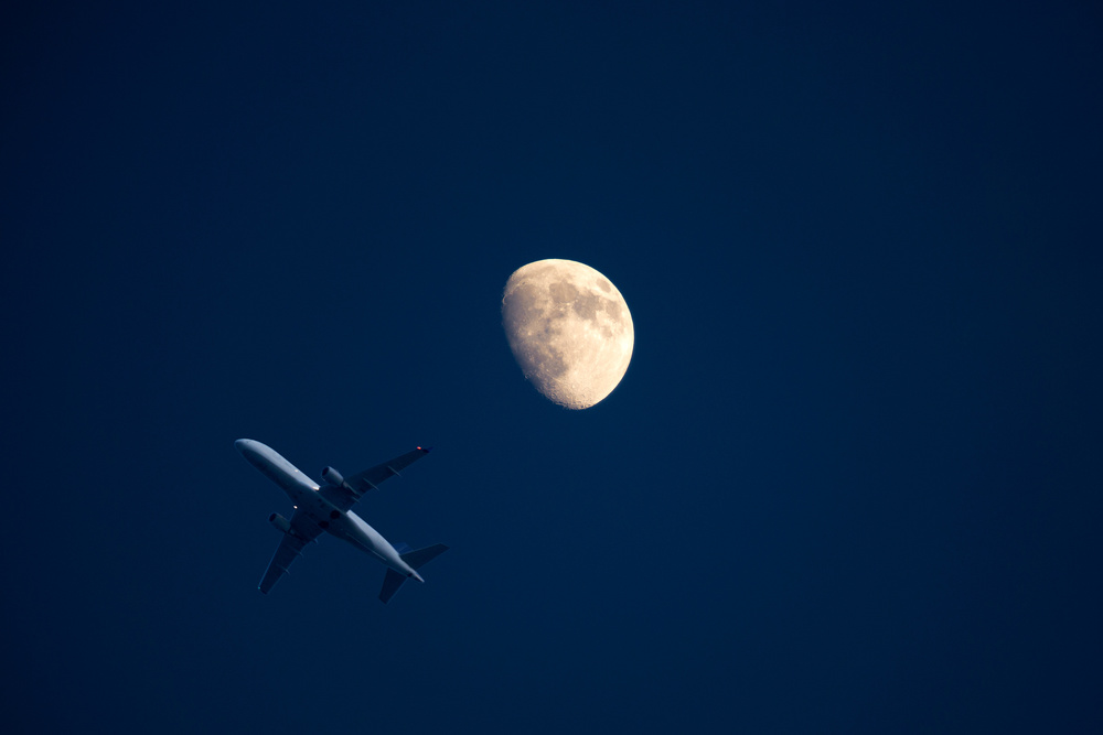 Plane landing in LaGuardia airport, New York. The photo was taken from a rooftop in Brooklyn. I was taking pictures of the moon when a plane got in the shot.