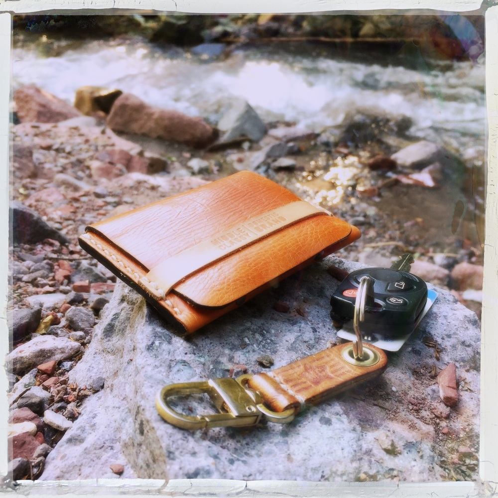 The 454 wallet and The Gem keychain sitting stream side.