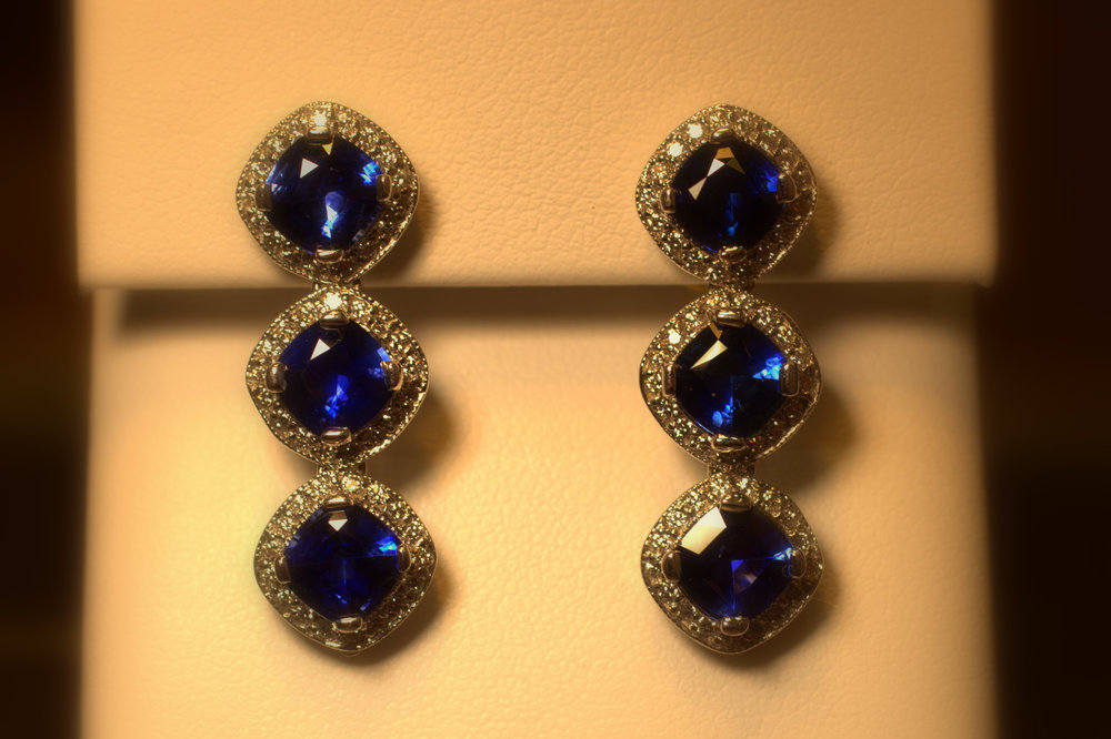 Stunning 3 sapphire drop earrings. Each sapphire has a diamond halo around it. The sapphires have perfect color that display great fire and sparkle with amazing diamonds around them. This is truly an eye-catching piece that will be loved by anyone. $12,500