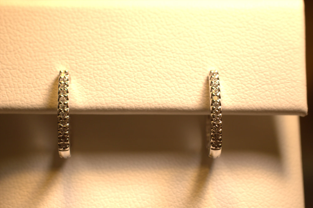 Shared prong diamond hoop earrings. White gold bright white diamonds sparkle small but eye-catching. These are extremely comfortable and perfect for everyday wear. This is a great gift to give as a first pair of diamond hoops. $1500