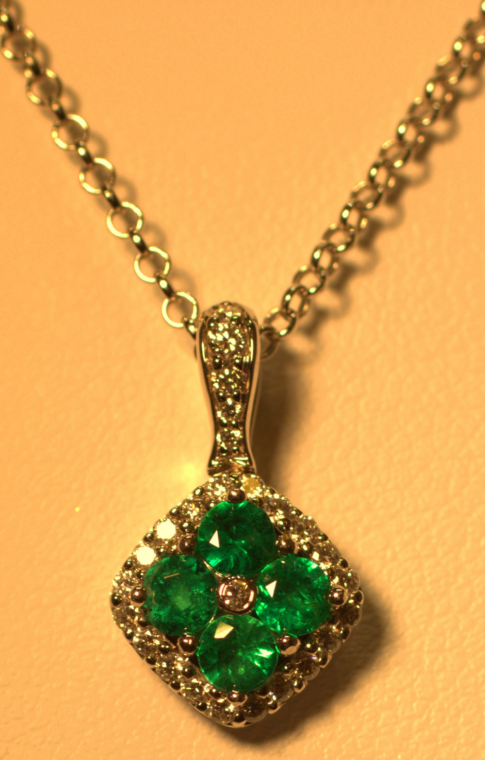 Beautiful green emerald and diamond cluster pendant. Pave diamond set bail. Diamond halo around 4 gorgeous columbian emeralds. The vibrant green color truly sparkles. $1800