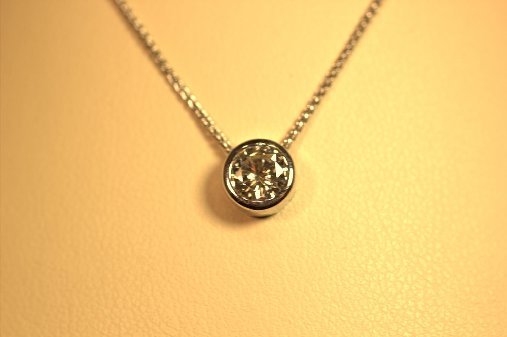 Bezel set diamond pendant, perfect in any size gives, a little flair to a classic piece. Very hot chic styling, minimalistic but a .50 carat well cut truly sparkles.  $1500