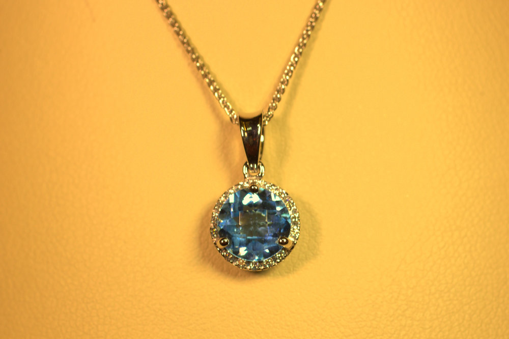 Checkerboard finish blue topaz swiss blue stone with diamond halo. White gold bail and chain modern take on a classic look very chic.  $750