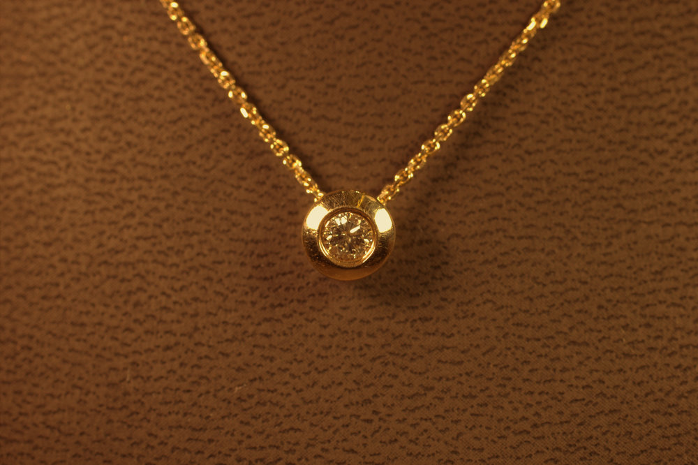 Classic Tiffany donut bezel set diamond pendant .2 carat diamond yellow gold bezel and chain pops and sparkles. Very chic piece, a modern take on a classic. $500