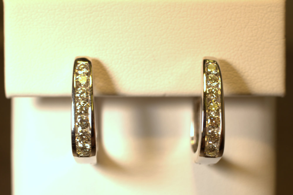 Diamond hoop earrings are a classic staple in any woman's wardrobe. Channel set diamonds set in white gold sparkle in these earrings. Very eye catching and the squared bottom makes the unique.  $2400
