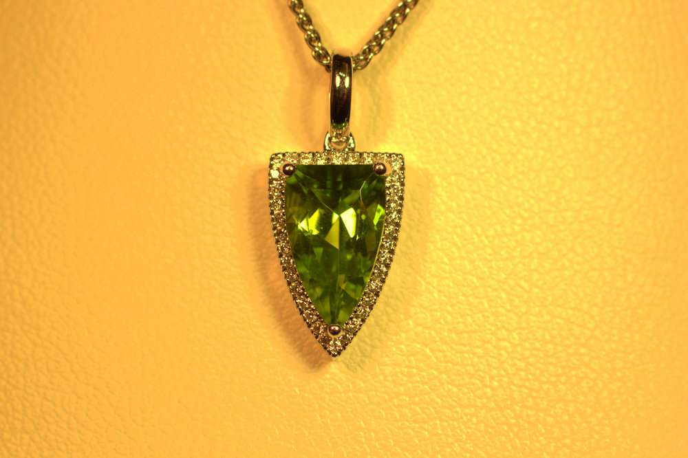 Diamond cut peridot stone creates an amazing green color with lots of sparkle. The shield-shaped diamond halo creates very modern look  with a very different shape. $1500