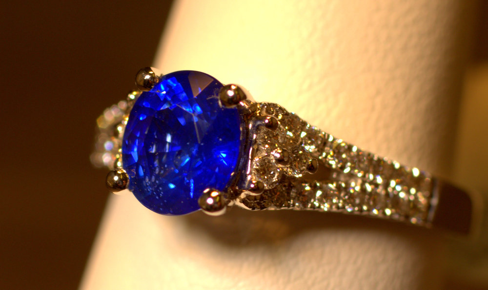 This oval-shaped sapphire is diamond cut, giving off a beautiful blue glow with plenty of sparkles. The ring features diamonds down each side. $5000