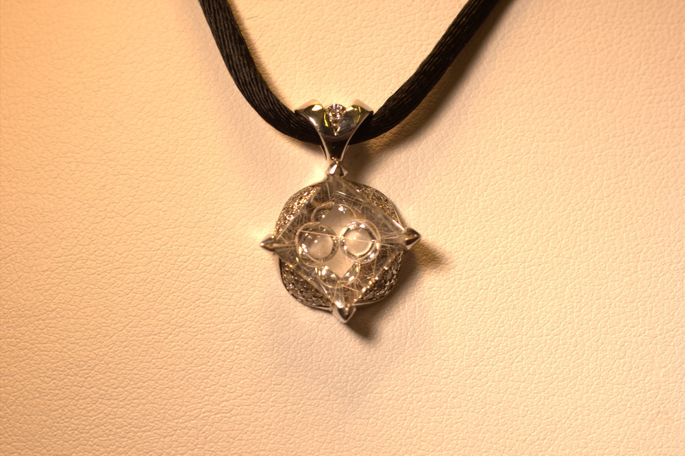 Mark Schneider custom designed white gold and diamond rutilated quartz pendant on a black silk cord. Tom Munsteiner quartz has needlelike crystals. Modern and chic.  $4500