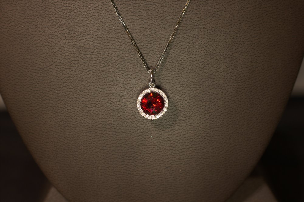 Modern styling vintage diamond halo surrounds a beautiful garnet.  Ideal cut diamonds provide incredible sparkle.  $925