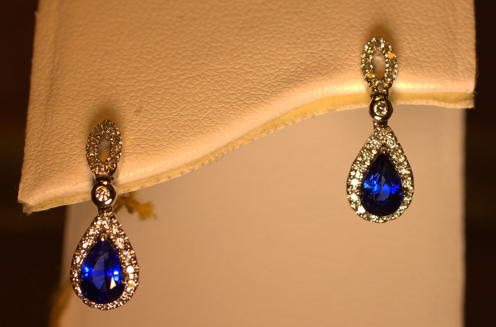 Teardrop shaped blue sapphire diamond earrings. Diamond circle on the ear drops down to the diamond halo that surrounds beautiful sapphires. $2500