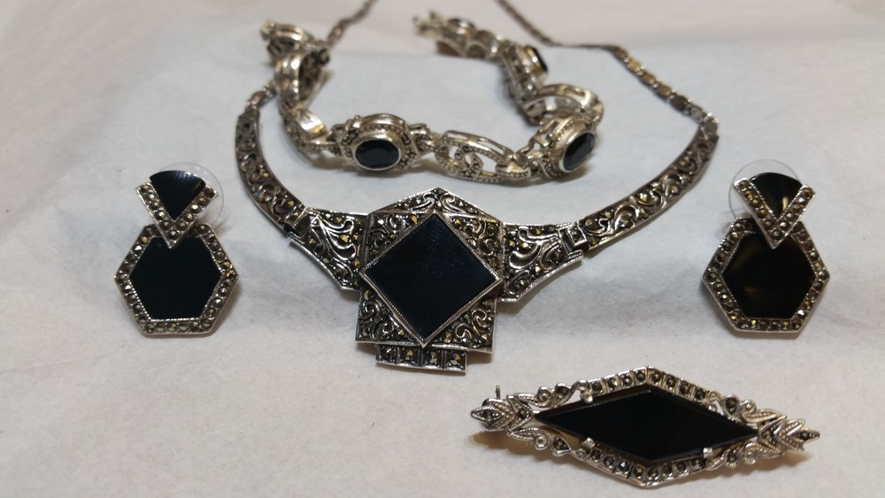 One of a kind set of antique jewelry. This set includes a pair of onyx earrings with a hematite border, an onyx broach pin with hematite side and a beaded and hand engraved edges, an onyx station bracelet with hematite accents and a filigree swirl onyx necklace with hematite throughout the piece. Hematite is a grey stone that if faceted correctly gives off sparkle comparable to antique diamonds. This is a very interesting set and not something you can find anymore. Sold individually or as a set. Set $400 Earrings $100 Pin $50 Necklace $200 Bracelet $150