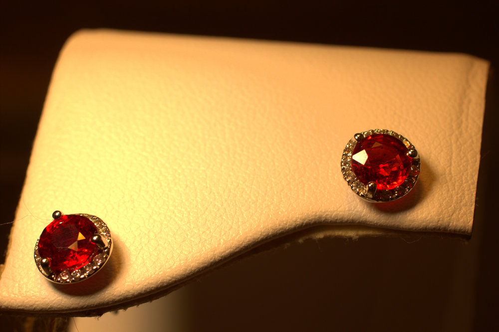 Ruby studs with diamond halo beautiful orgish red ruby studs with bright white sparkling diamonds classic with a modern touch very durable wear daily at Marlen Jewelers in Rocky River minutes from Cleveland.jpg