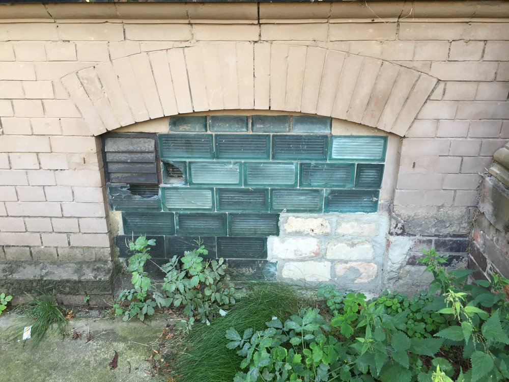 A basement window of House 3, sealed with multi-plated glass and bricks. The former detention cells are now used as administrative offices.