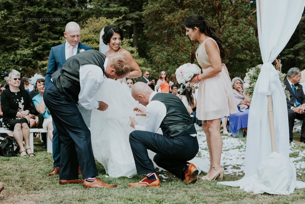 groomsmen helping bride fix dress at wedding ceremony | victoria bc wedding photographer