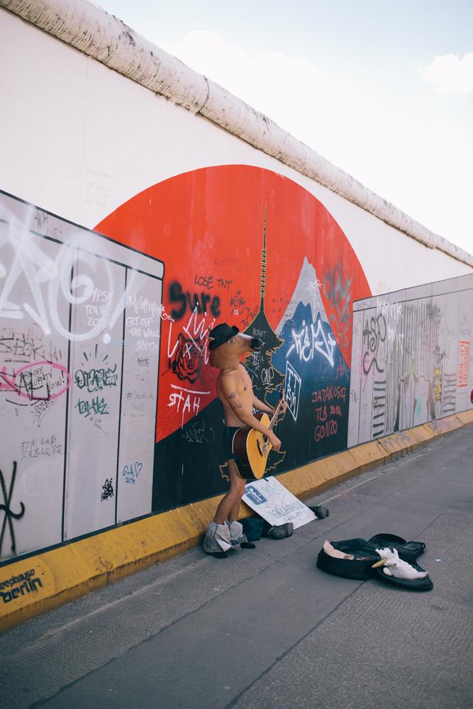 street performer alongside the wall