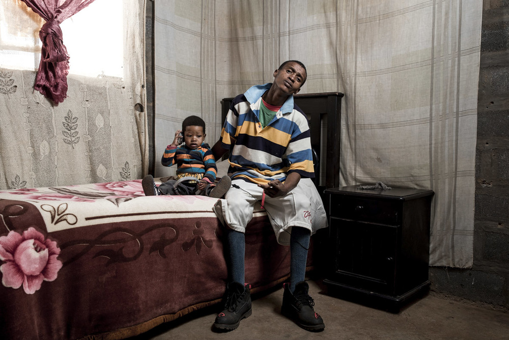 "Andre ""Bushy Bird"" Ntholo at home with his son."