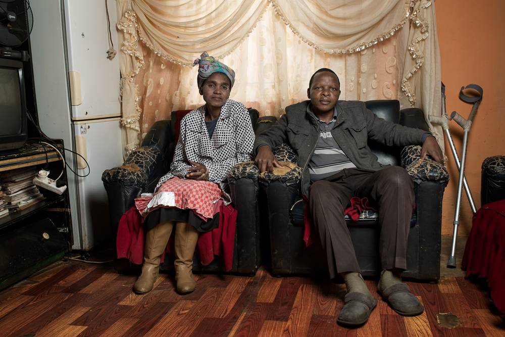 Landile Qebela , 52 years old, has nine children and works as a security guard now that he cannot work in the mines any longer. He has silicosis from his 32 years service at Vaal Reefs Shaft No 8 and received R52 000 compensation in 1995 (approx. £2,460 or $3,730). He stayed at the mine for another 5 years working as a locomotive driver on the surface until he was retrenched because they could not find a suitable job for someone so sick. Mr Qebela went to find work in the mines when he was 25 years old because his mother became sick and he needed to make money to provide for his sister's future. He managed to send enough money home over the years to support her until she gained her teacher's certificate.